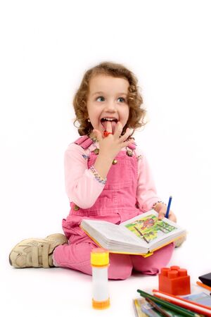 The small cheerful girl in pink jeans with the book in a hand, on a white background Stock Photo