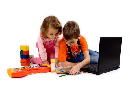 Children with the computer, pencils, CD, school writing-materials around