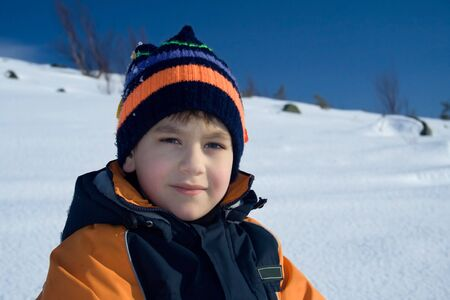Portrait of the steadfastly looking boy on a background of polar snow plain