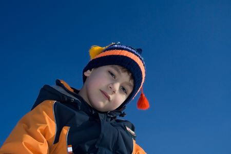 Portrait of the steadfastly looking boy on a background of the dark blue sky Stock Photo