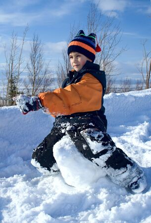 straddle: The boy to straddle a snow ball on a background of polar mountains Stock Photo