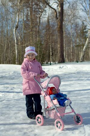 The girl in a pink jacket with a pink toy carriage on walk in park