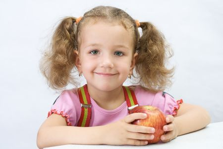 Portrait of the pretty girl with an apple, over white