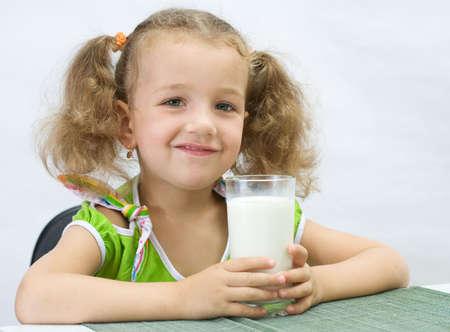 The girl drinks for breakfast milk, over white