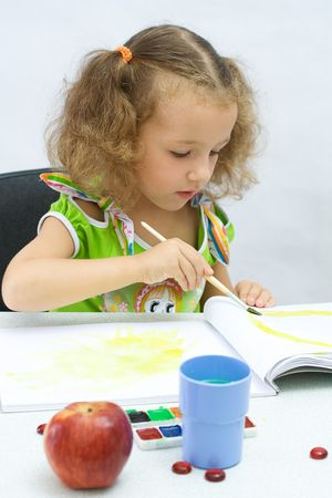 The girl draws by paints in an album photo