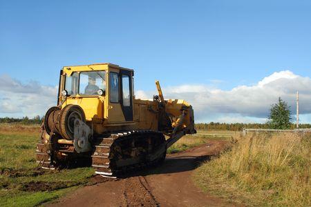 Yellow grader on rural road photo