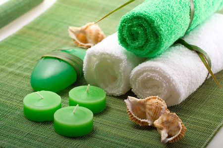 Spa concept of green color: the towel, soap and candles over sisal background