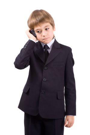 Boy in a business suit with a telephone, isolated over white