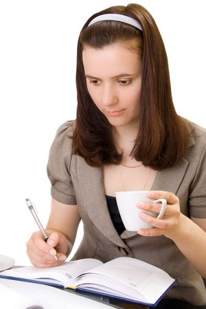 Girl keeps cup coffee and does record in notebook, isolated photo