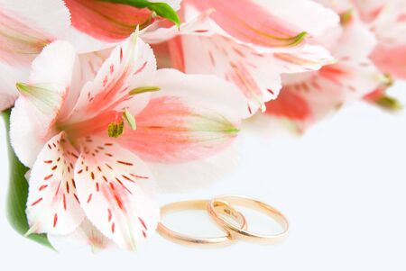 Bouquet of Alstroemeria and wedding rings on the white Stock Photo