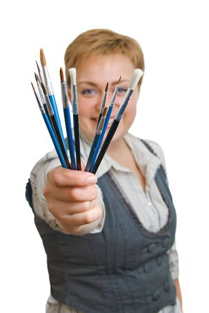 Smiling girl with a paintbrush, isolated over white, focus on the brush photo
