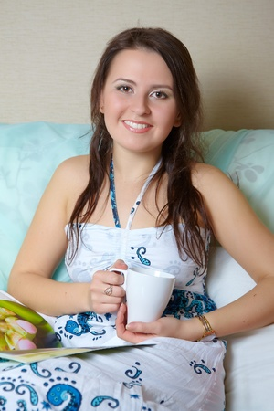 Portrait of happy young woman holding cup of coffee photo
