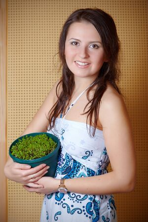 Young beautiful woman with small plant in flowerpot photo