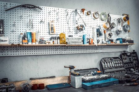 Moto workshop with hand mechanic tools kit. Workbench with sets of keys, screwdrivers, ploskobets, electrical tape, duct tape on wall. Table with motorcycle parts, vise. Workspace for auto mechanic