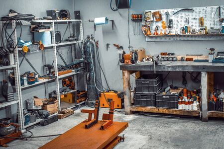 Garage, service area for disassembling, repairing motorcycles, car service station. Inside the workshop with large workbench, shelving, moto lift, tools kit for processing wrenches on the wall