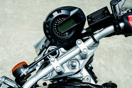 Combined electronic speedometer and dial tachometer on the steering wheel of a sports motorcycle. Control panel with turn signal and motobike signal button close-up on a concrete background.