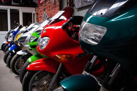Colored sports, road beautiful bikes in a motor show, close up. Many motorcycles parked in a store. Sale of used cruise motorbikes in the cabin. Showroom equipment in the garage.