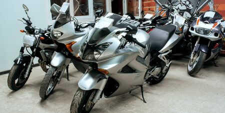 Gray sports beautiful bikes in a motor show. Many motorcycles parked in a store. Sale of motorbikes in the cabin. Exhibition garage equipment. Banner for web site Stock fotó