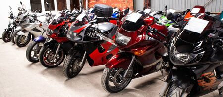 Colored sports, road beautiful bikes in a motor show. Many motorcycles parked in a store. Sale of used cruise motorbikes in the cabin. Showroom equipment in the garage. Banner for web site