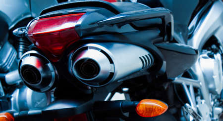 Exhaust pipes and brake light of a motorcycle closeup. The noise of a sports bike in a garage. Rear view of a classic road bike. A pair of chrome pipes selective focus. Banner for web site Imagens