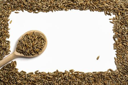 Rectangular frame of grains of wheat, barley, rye, oat with a wooden spoon on white background close up, isolated. Cereal seeds for site with inscription, top view. Free space for text in the center Foto de archivo