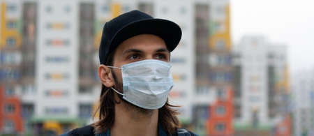 Handsome young man in regular disposable surgical, medical mask on the street in city. Coronavirus, covid-19 protection. Banner for web site. Portrait made in side closeup. Gaze is directed to right