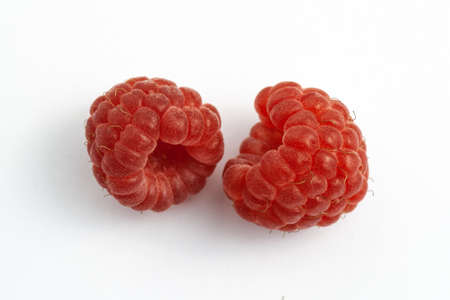 Two ripe raspberries isolated on a white background close-up. Fresh raspberries without sheets on the table. Macro shooting. Healthy, wholesome food. Top view. 免版税图像