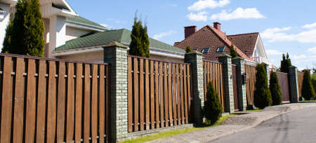 Wooden fence made of concrete pillars on an empty street in a cottage village Outdoor landscape. Security and privacy concept. Roofs of beautiful houses behind gates. Banner for web site Stockfoto