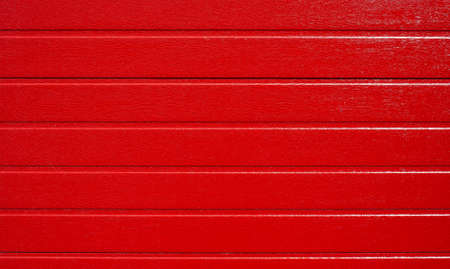 Red wooden background, horizontal striped texture. Folding garage door made of metal profile, red carbon. Red corrugated wall