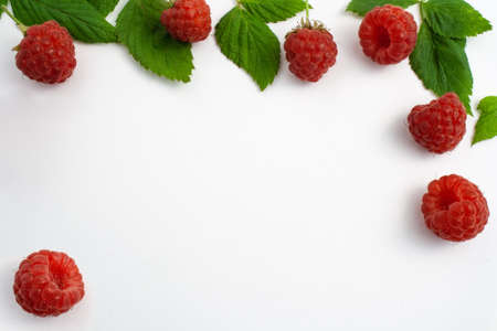 Ripe raspberries isolated on white background close-up. Beautiful red fresh raspberries with leaves along the contour on the table. Top view. Free space for text