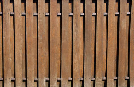 Wooden fence with vertical slats. Natural brown wood planks, wood texture background pattern. Fencing construction in sunny weather. Banner for web site