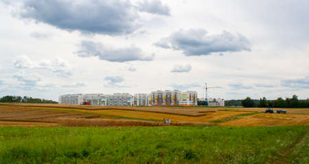 Panorama of large wheat field of cereals during the harvest with combine, people and tractor, against backdrop of new urban neighborhood with crane while building house with blue sky and clouds.