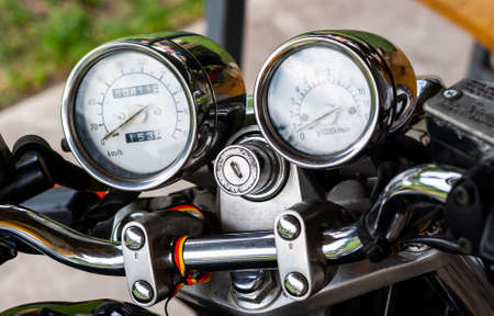 Pointer chrome speedometer and tachometer with a keyhole on the handlebars of a motorcycle close-up on a colored background. Colored shiny dashboard of an old-style sports motorcycle, side view.