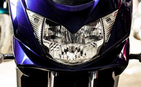 Big headlight front view of motorcycle in showroom with soft-focus, close up. Glossy purple windproof shield with headlight of sportbike. Front part of modern motorcycle in salon, with steering wheel