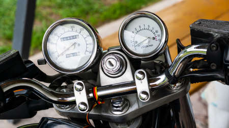 Pointer speedometer and tachometer with a keyhole on the handlebars of a motorcycle close-up on a colored background. Colored dashboard of an old-style sports motorcycle, top view.