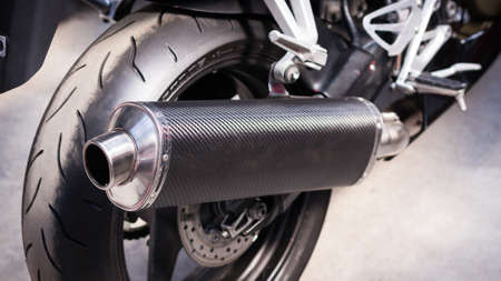 Back of modern sports bike, bottom side view, close-up. Carbon exhaust pipe, brake disc, alloy wheel, engine, rear wheel, motorcycle. Road fast motorcycle in garage for repair, maintenance. Moto tire