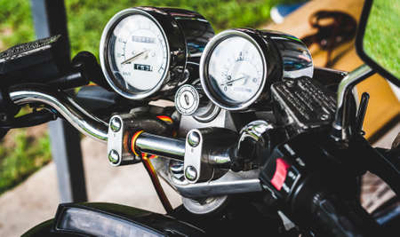 Pointer chrome speedometer and tachometer with keyhole on handlebars of motorcycle close-up on colored background. Colored shiny dashboard of an old-style sports motorcycle, side view. Banner site Banque d'images