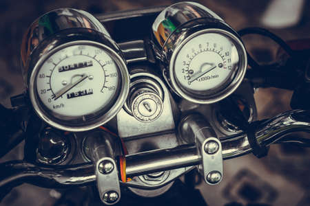 Pointer chrome speedometer and tachometer with a keyhole on the handlebars of motorcycle close-up on colored background. Colored shiny dashboard of an vintage old-style sports motorcycle, side view. Banque d'images