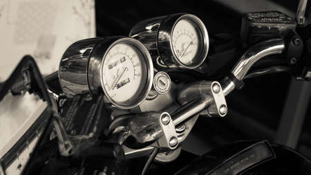 Pointer chrome speedometer and tachometer with keyhole on the handlebars of a motorcycle close-up in garage. Monochrome dashboard of an old-style sports motorcycle, side view. Black and white photo