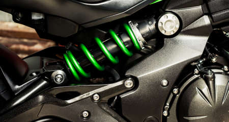 Green shock absorber with spring and black cylinder of engine of motorcycle closeup. Part sport bike, side view. Motorcycle chassis, internal combustion engine and frame bike. Banner for web site