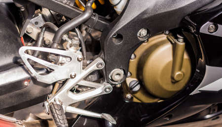 Gold engine of motorcycle close-up. Sport silver-black bike, top side view. Motorcycle internal combustion engine with cylinder, engine air cooling system, carburetor, fuel system, wheels, steps