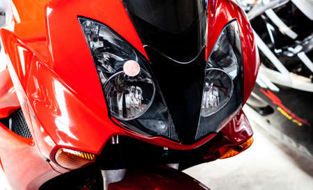 Pair headlights front side view of motorcycle in showroom close up. Glossy red-black windproof shield with headlights of sportbike. Front part of modern motorcycle in salon, with steering wheel Banner