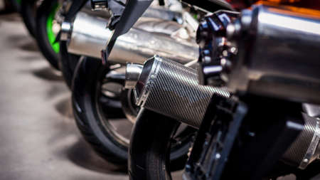 Many motorcycle parking in right way and orderly in one line. Exhaust pipes, rear wheels. Backs of modern sports bikes, side view, close-up. Road fast motorcycle in garage for repair. Moto tire.
