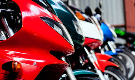 Sports motorcycles lined up in showroom in store. Front part road bikes stand in shop for sale. Maintenance, repair of motorcycle equipment in garage. Handlebars, shock absorbers, wheels, headlights Stockfoto