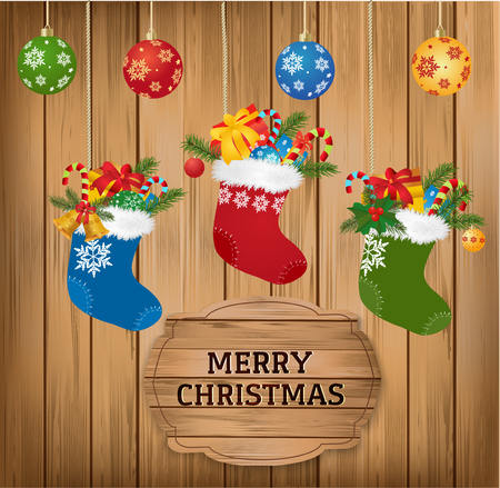 fir branch: Christmas baubles and stoking with fir branch, candy cane and gifts on wooden background with Merry Christmas greetings text.