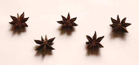 Five whole anise stars on a white background