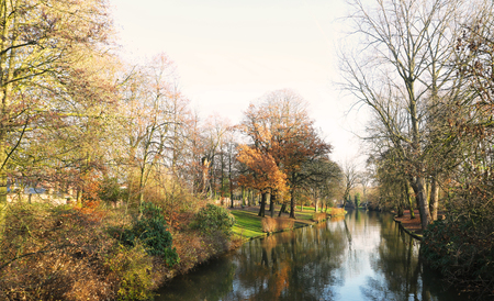 Picturesque autumn landscape with bright blue sky, yellow leaves and steady river in Brugge, Belgium