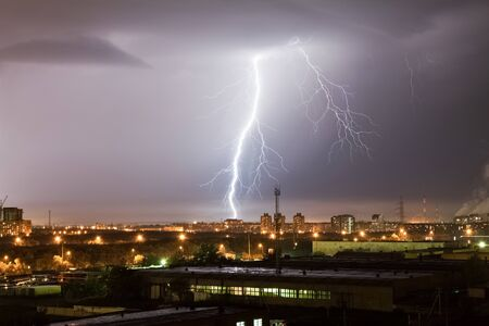A powerful lightning strike hits the city at night. A strong lightning strike over a dark gray sky hits the ground, illuminating the industrial area around.
