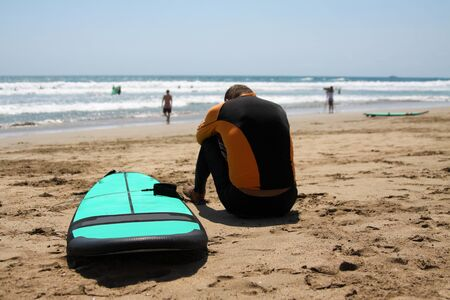 Beginner surfer in a bathing suit is sitting on the wet sand on the ocean. His head is bowed on folded hands. There is a surfboard next to it. Surfer very sad because he is upset about the failure. Stock Photo