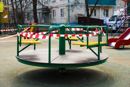 It is forbidden to visit playgrounds,they are closed for prevention of coronavirus pandemic. A warning tape is block the swing. Protection against contagious covid-19. The children stay at home